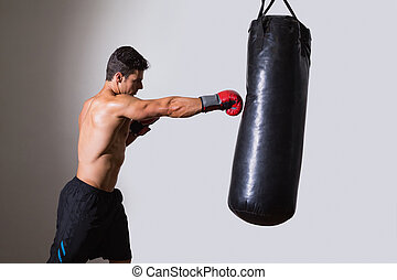Shirtless muscular boxer with punching bag