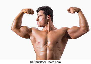 Portrait of a muscular young man flexing muscles over white...