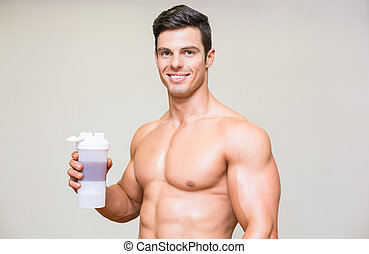 Close-up portrait of a sporty young man with protein drink...