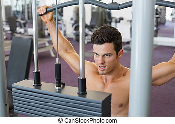 Muscular man exercising on a lat machine in gym - Close-up...