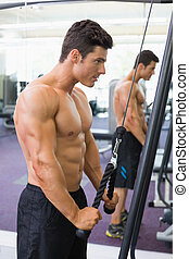 Shirtless muscular man using triceps pull down in gym - Side...