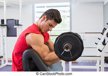 Muscular man lifting barbell in gym - Side view of a...