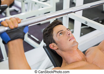 Shirtless muscular man lifting barbell in gym - High angle...