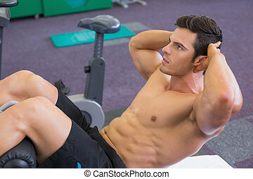 Muscular man doing abdominal crunc - Side view of muscular...