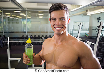Sporty young man with energy drink in gym - Close-up...