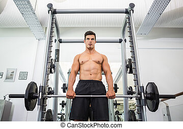 Shirtless muscular man lifting barbell in gym - Low angle...