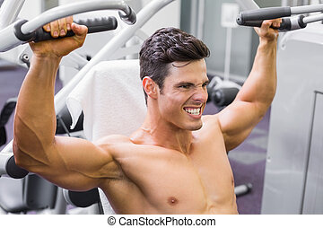 Muscular man working on fitness ma - Determined young...