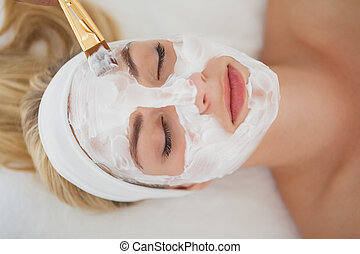 Beautiful blonde getting a facial treatment at the health...