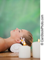 Peaceful blonde lying on bamboo mat with candles at the...
