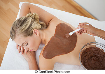 Beautiful blonde enjoying a chocolate beauty treatment at...