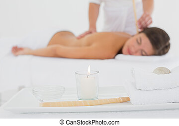 Beautiful woman receiving ear candle treatment at spa center...