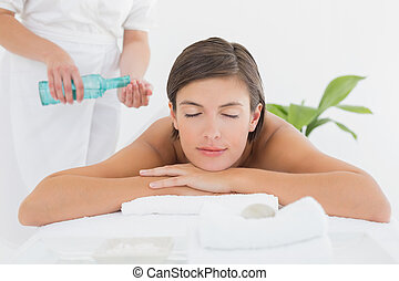 Attractive woman getting massage oil on her back