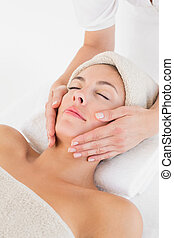 Attractive woman receiving facial massage at spa center -...