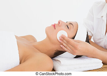 Hand cleaning woman's face with cotton swabs at spa center