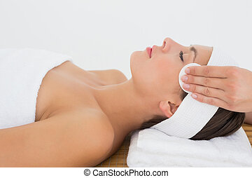 Hand cleaning womans face with cotton swabs at spa center