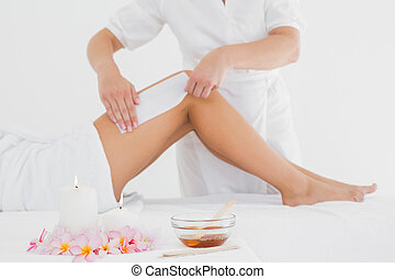 Therapist waxing womans leg at spa center - Mid section of...