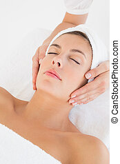 Attractive young woman receiving facial massage at spa...
