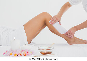 Therapist waxing womans leg at spa - Mid section of...