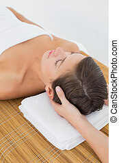 Attractive woman receiving head massage at spa center -...