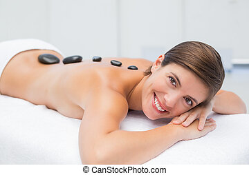 Beautiful woman receiving stone massage at spa center -...