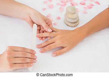 Beautician filing female client's nails at spa beauty salon...