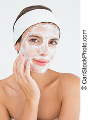 Attractive having white cream on her face at spa center -...