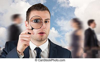 Composite image of businessman looking through magnifying...