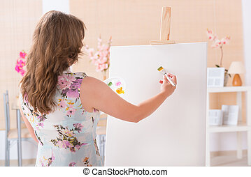 Artist at work - Beautiful woman painting on canvas at her...