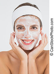 Attractive woman having white cream on her face - Close-up...