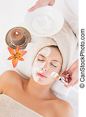 Attractive woman receiving treatment at spa center - High...