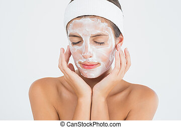 Attractive woman having white cream on her face at spa...