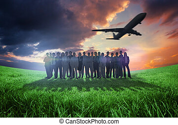 Composite image of business people standing up with airplane...