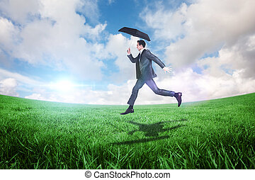 Composite image of businessman jumping holding an umbrella -...