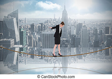 Composite image of businesswoman performing a balancing act...
