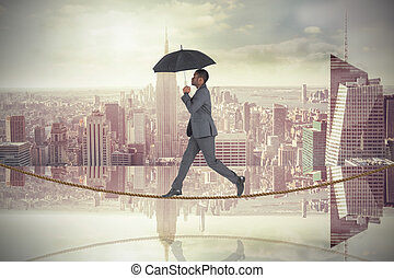 Composite image of businessman walking on tightrope and...