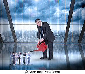 Composite image of mature businessman watering tiny business...