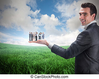 Composite image of businessman holding business team against...