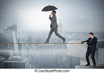 Young business man pulling a tightrope for businessman...