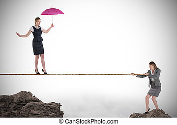 Young business woman pulling a tightrope for businesswoman...