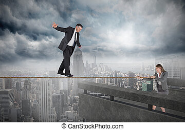 Young businesswoman pulling a tightrope for businessman...