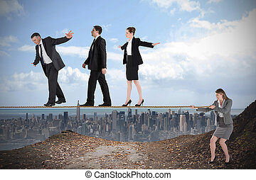 Young businesswoman pulling a tightrope for business people...