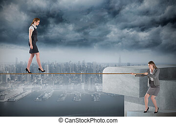 Young businesswoman pulling a tightrope for business woman...