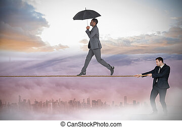 Young businessman pulling a tightrope for business man...