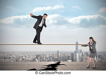 Young businesswoman pulling a tightrope for businessman -...