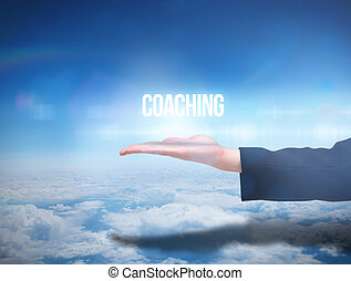 Businesswomans hand presenting the word coaching against...