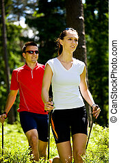 nordic walking in forest - a couple nordic walking in the...