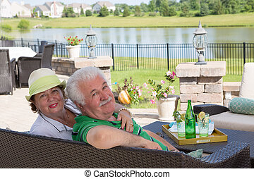 Elderly couple enjoy a relaxing day on the patio -...