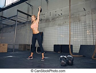 Female athlete in a crossfit workout - Young fitness woman...