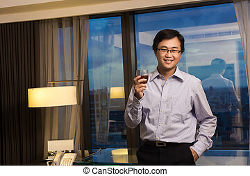 Asian business man take a glass of whisky and look at you in...