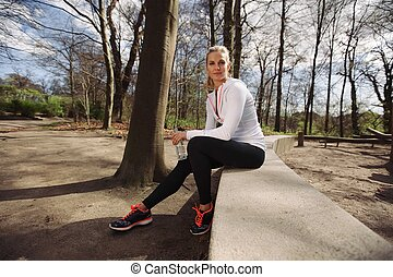 Female runner taking a rest from training in nature....
